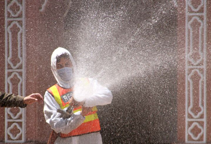 Ein Mitarbeiter des Gesundheitswesens sprüht Desinfektionsmittel in einer Moschee