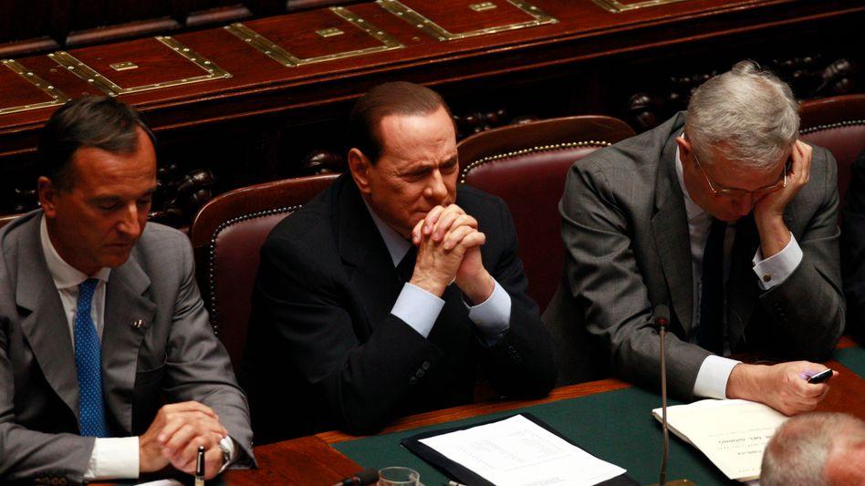 Regierungschef Silvio Berlusconi (M.): 2013 soll der Haushalt ausgeglichen sein