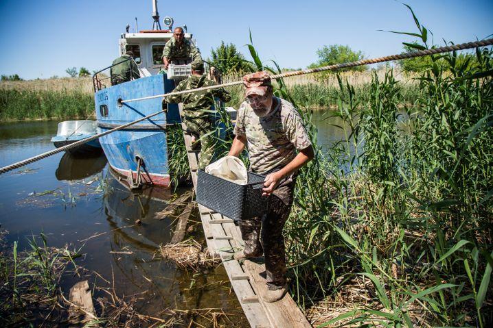 Sergej beim Tragen seiner Ausrüstung auf das Schiff seiner Behörde nahe Gornij Balyklej