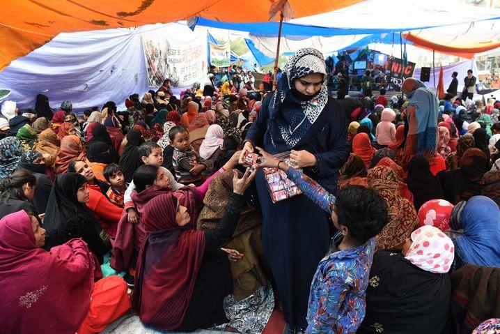 Freiwillige verteilen Kekse an die Demonstranten in Shaheen Bagh