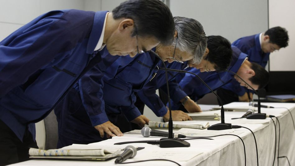 TEPCO bosses bow at the end of a news conference at the company headquarters in Tokyo.