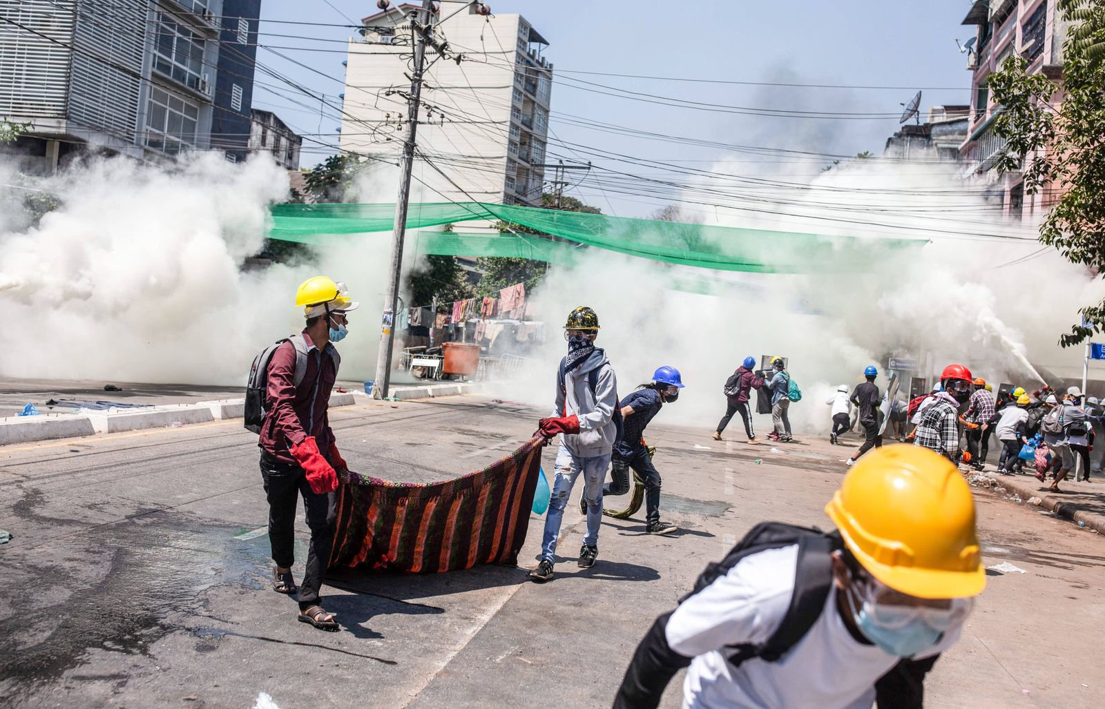 March 7, 2021, Yangon, Myanmar: Protesters react after riot police fired tear gas canisters during a demonstration agai