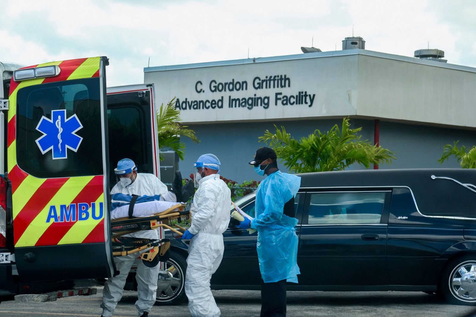 FILE PHOTO: Emergency Medical Technicians (EMT) arrive with a patient while a funeral car begins to depart at North Shore Medical Center where the coronavirus disease (COVID-19) patients are treated, in Miami