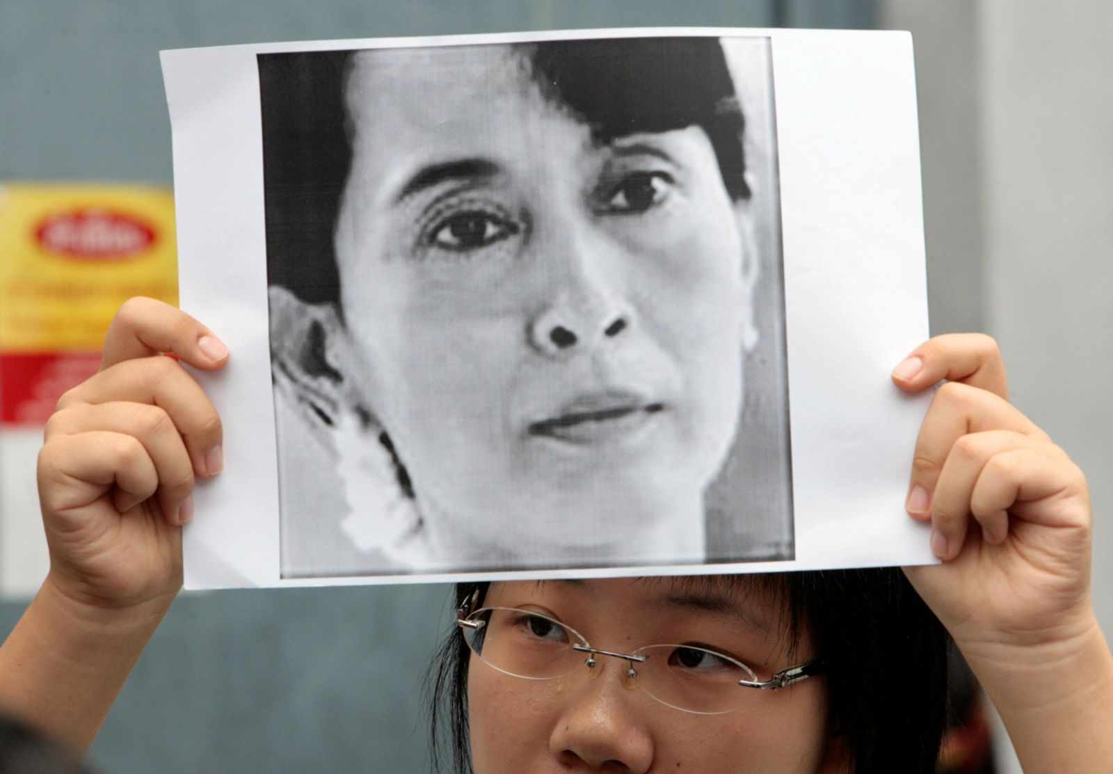 A woman from Myanmar holds a portrait of Myanmar's opposition leader Aung San Suu Kyi outside the Myanmar embassy in Bangkok