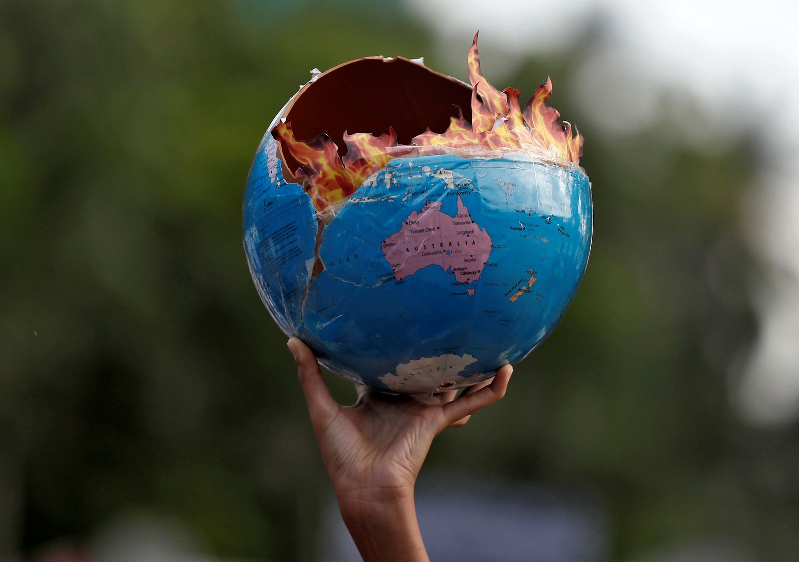 """A participant holds a replica depicting globe on fire during a """"Fridays for Future"""" march calling for urgent measures to combat climate change, in Mumbai"""