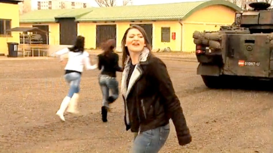 """A still from the Austrian army video showing young women running after a departing tank in the hopes of going on a """"joy ride."""""""
