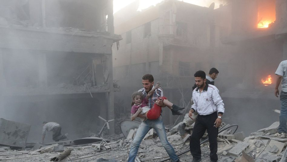 A man carries a girl in the Douma quarter of Damascus following shelling by regime troops.