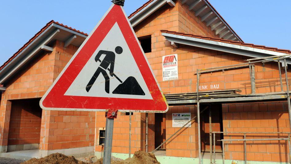 Baustellenschild steht vor einem Rohbau: Vorsicht bei der Bausparberatung