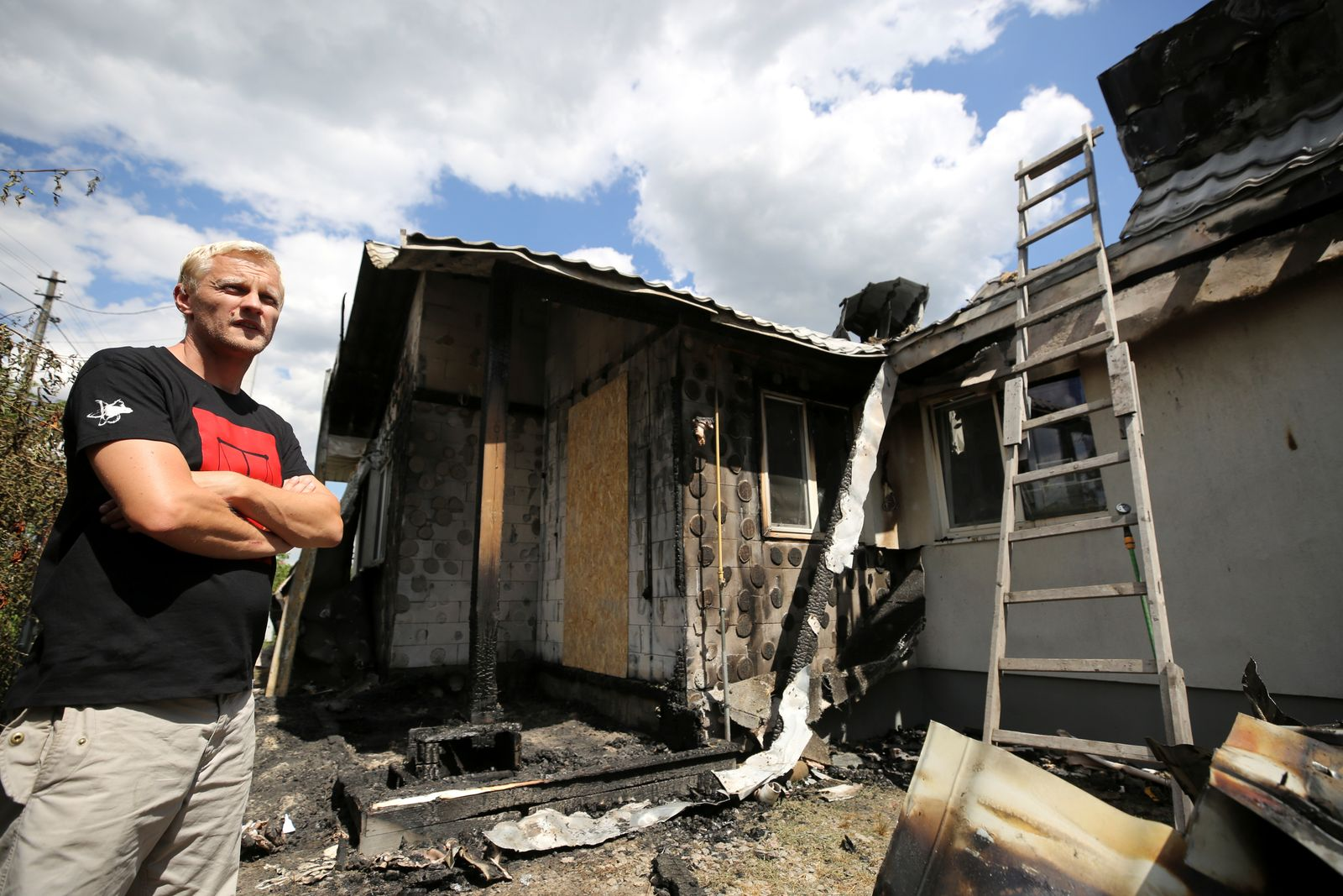 Ukrainian anti-corruption activist Vitaliy Shabunin stands next to his house, damaged by fire, in the village of Hnidyn