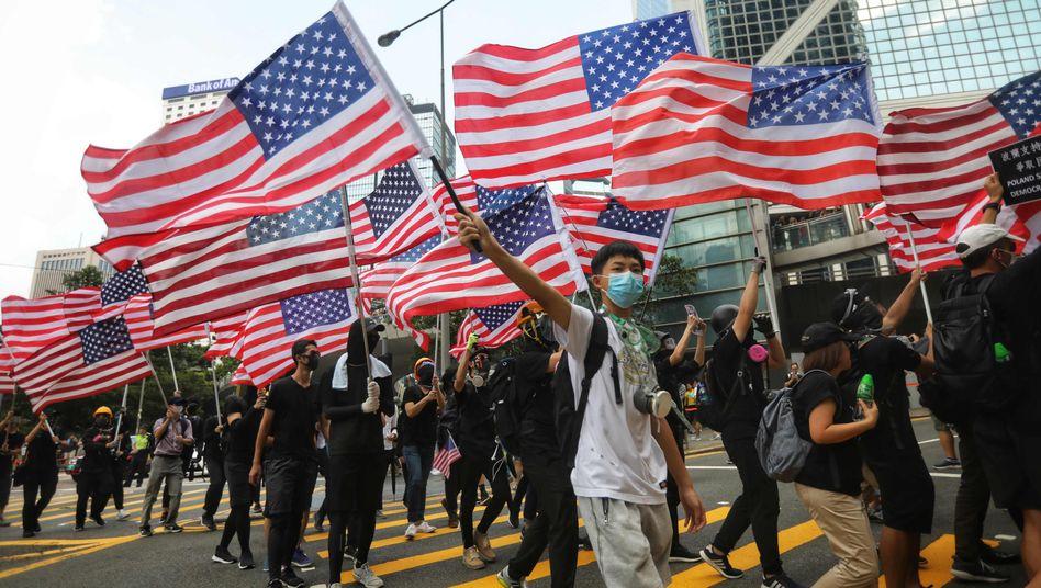 Flagge zeigen: Demonstranten ziehen mit der amerikanischen Nationalflagge durch die Straßen Hongkongs