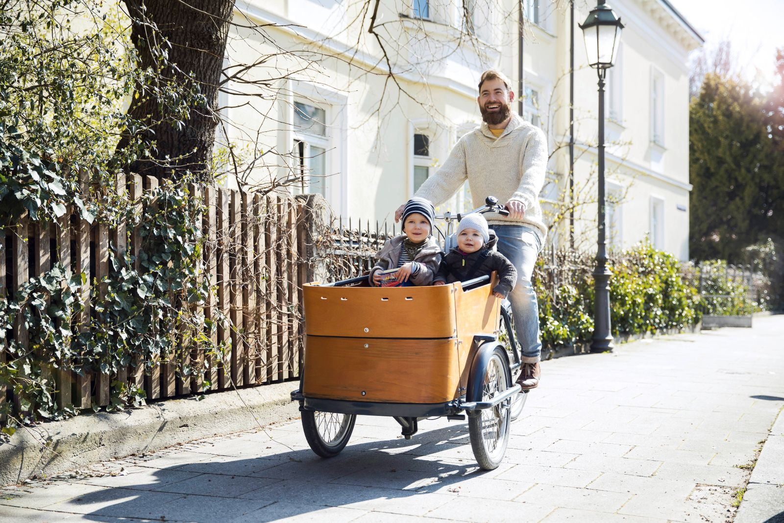Happy father with two children riding cargo bike in the city model released Symbolfoto PUBLICATIONxINxGERxSUIxAUTxHUNxO