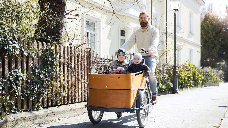 Ein Vater fährt mit seinen Kindern in einem Lastenfahrrad