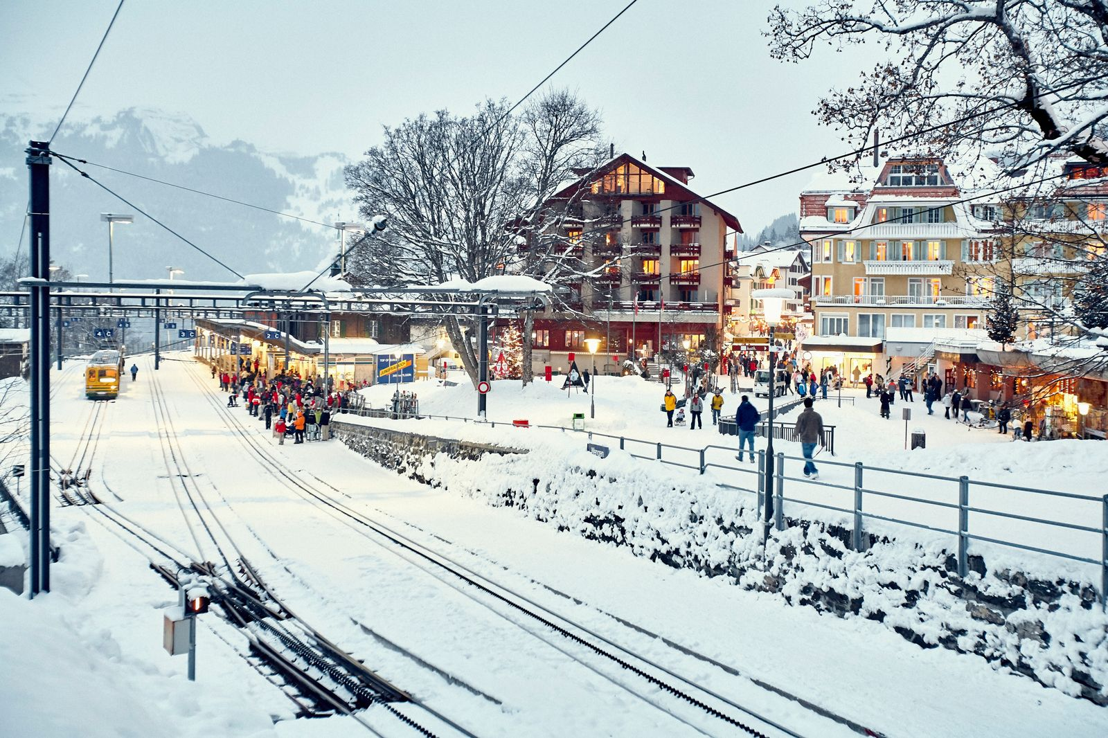 Crowds of passengers at snow covered train station, Wengen, Switzerland