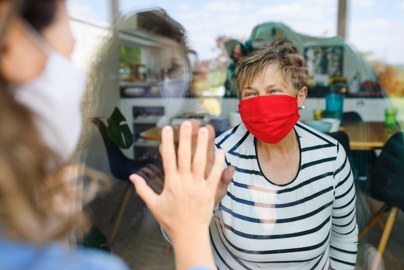 Woman with face mask greeting senior mother through glass, quarantine concept.