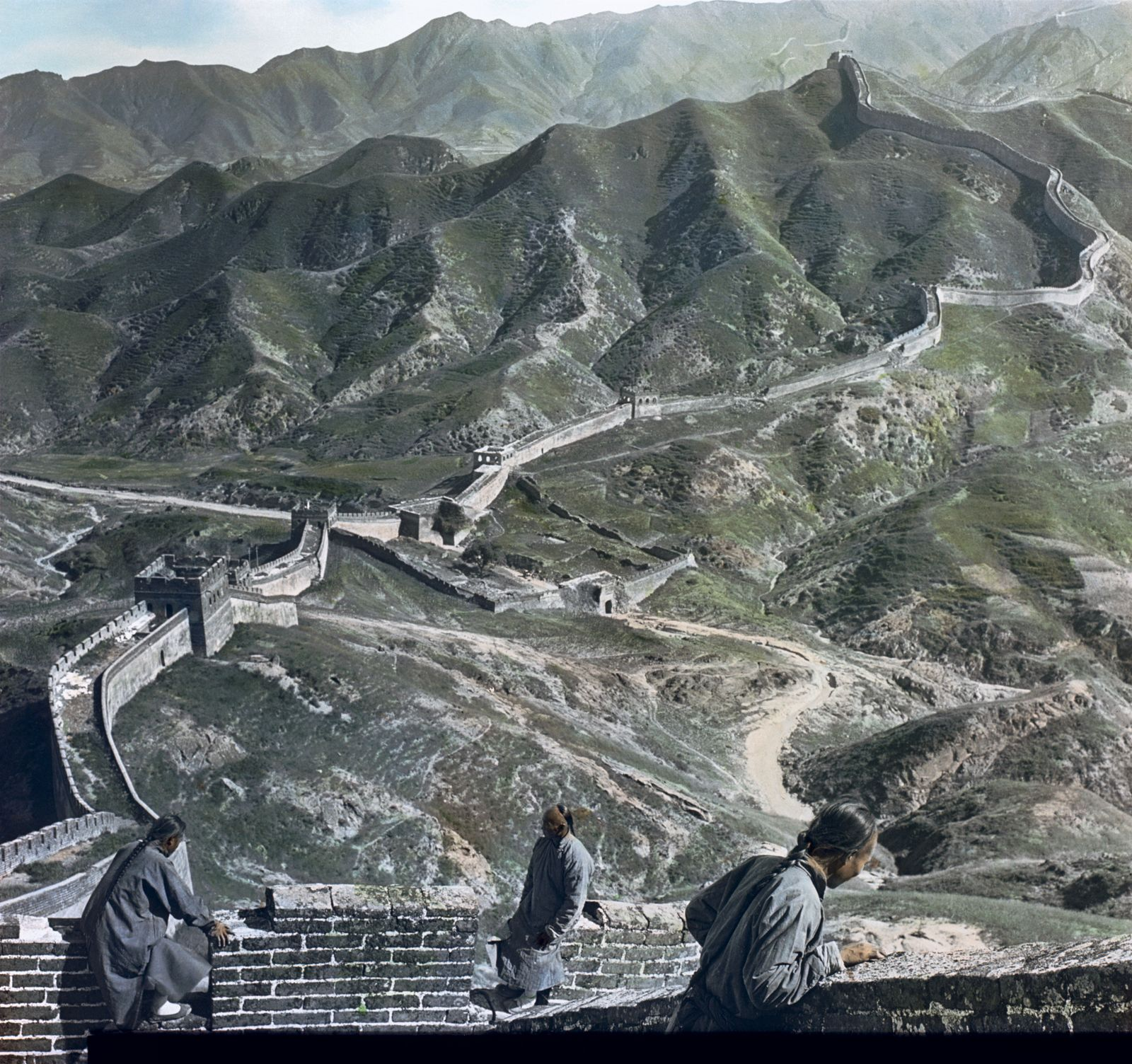 Colorized high angle view of men looking down at the land below from the Great Wall of China at one of the many mountain passes, China, 1901. (Photo by Burton Holmes). Image shot 1901. Exact date unknown.