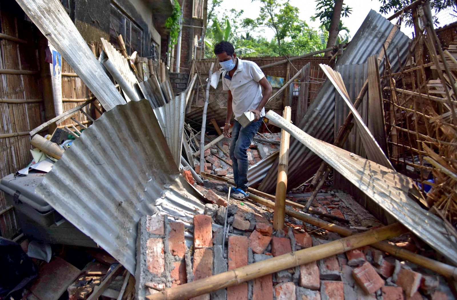 A man searches for his belongings amidst the debris after a boundary wall of his house collapsed following an earthquake in Nagaon