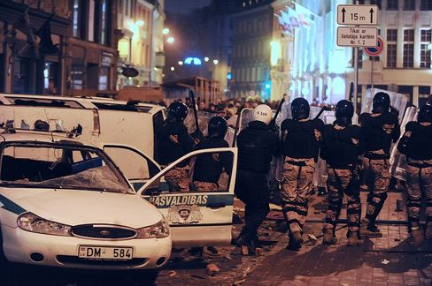 Riot policemen walk during clashes with demonstrators during a protest in Riga on Jan. 13.