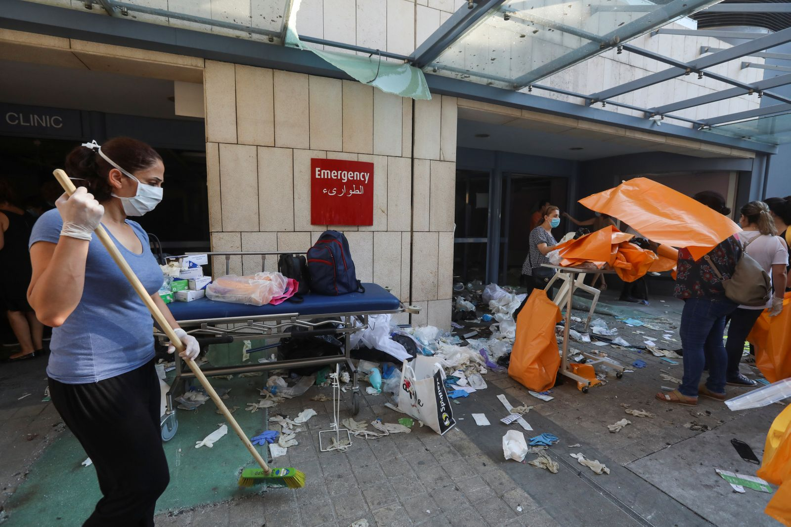 A woman sweeps at a damaged hospital following Tuesday's blast, in Beirut