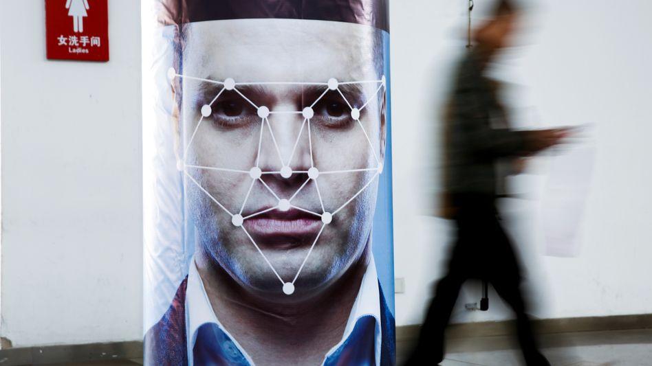 Ein Poster zeigt beispielhaft ein System zur Gesichtserkennung bei einer Messe in China (Archivbild)