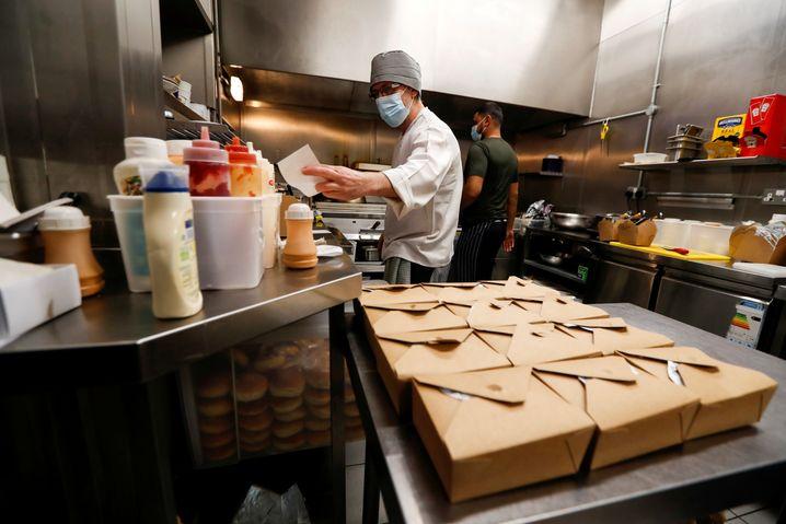 Ein Küchenchef vom »The Meating Room«-Restaurant bereitet warme Speisen für Familien zu, die auf kostenlose Schulmahlzeiten angewiesen sind