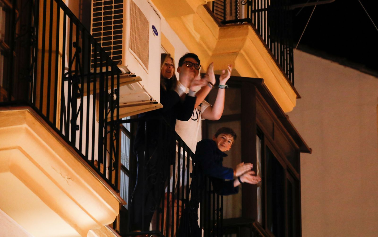 A family applaud from their balcony during a call on social media to thank Spanish medical staff fighting against coronavirus as they remain confined inside their homes due to the coronavirus outbreak, in downtown Ronda