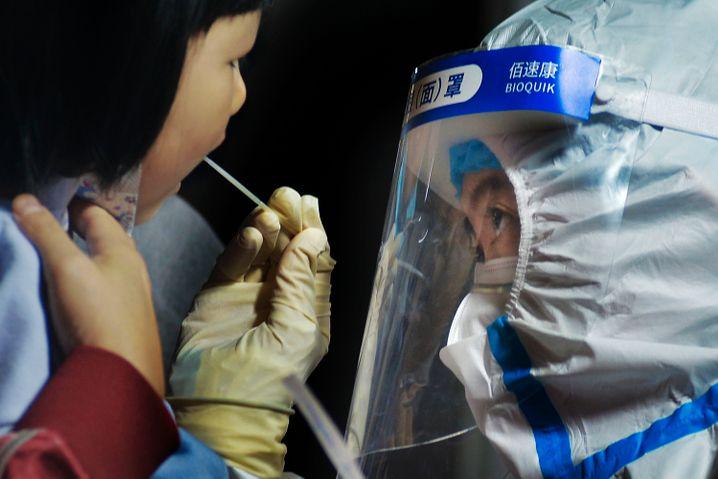 Medizinisches Personal nimmt einen Abstrich eines Kindes in Qingdao