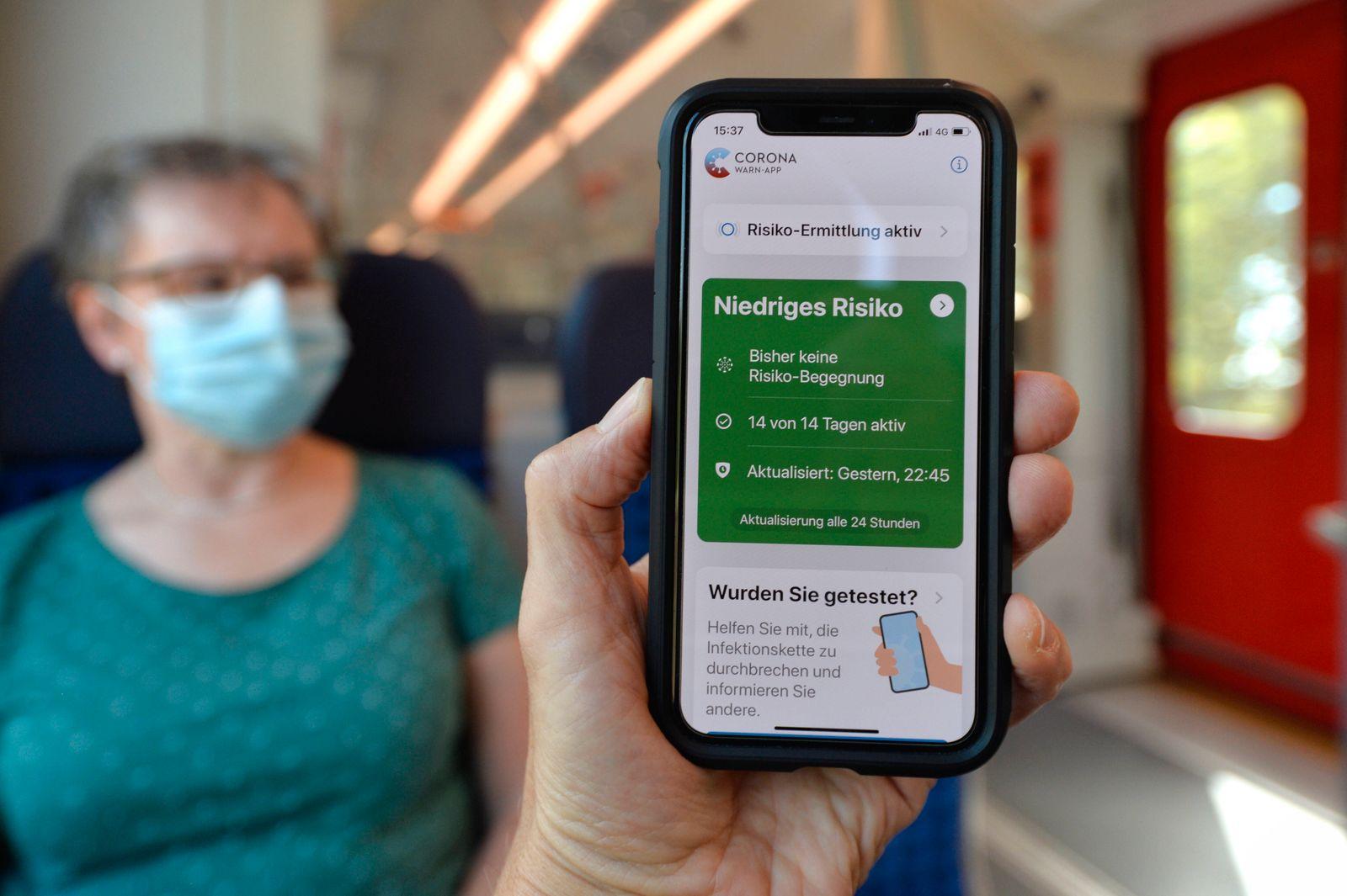 Hand hält Smartphone mit Corona Warn-App im grünen Bereich vor ältere Frau mit Mundschutzmaske sitzt in S-Bahn, Zug, Co
