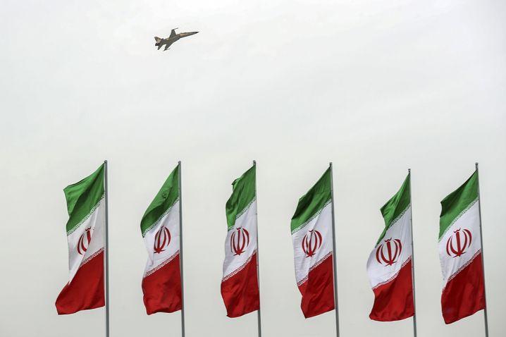 Iranischer Jet über iranischen Flaggen