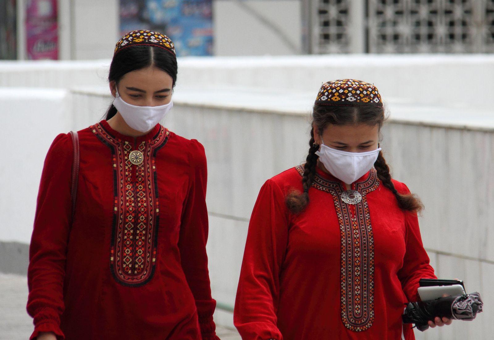 Women wearing protective face masks walk along the street in Ashgabat