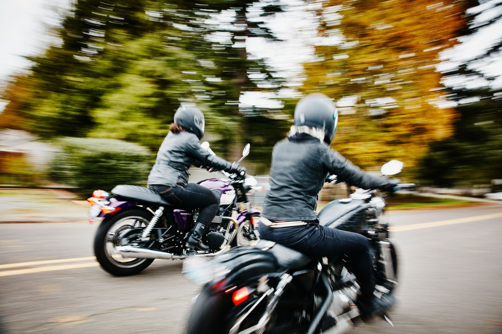 Two women riding motorcycles together down road