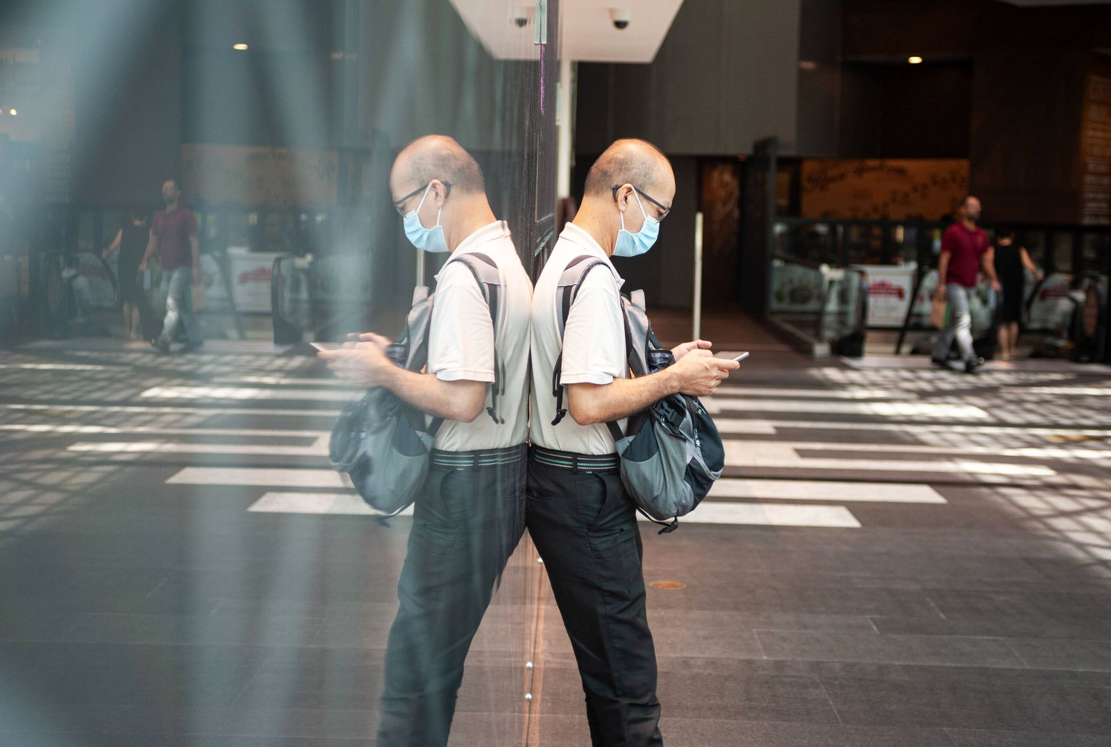 02.04.2020, Singapur, Republik Singapur, Asien - Ein Mann starrt im Raffles City Einkaufszentrum auf sein Handy und trae