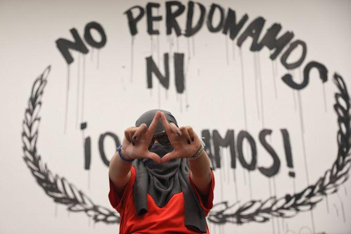 """""""Wir vergeben und vergessen nicht"""", warnt das Graffiti hinter einer Aktivistin"""