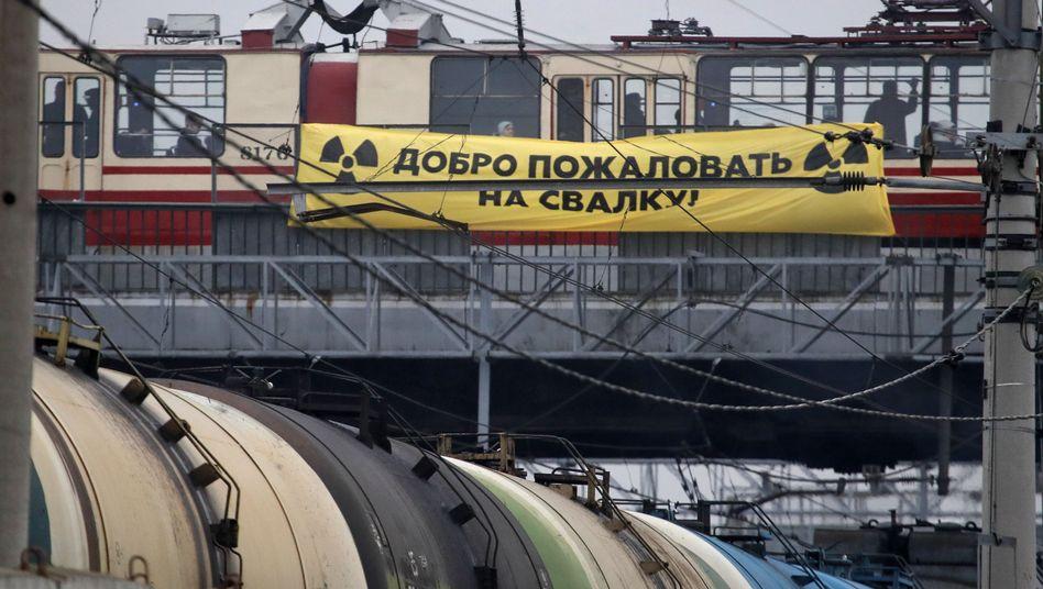 """""""Willkommen auf der Müllhalde"""" steht auf dem Banner, das Greenpeace-Aktivisten an einer Brücke angebracht haben"""