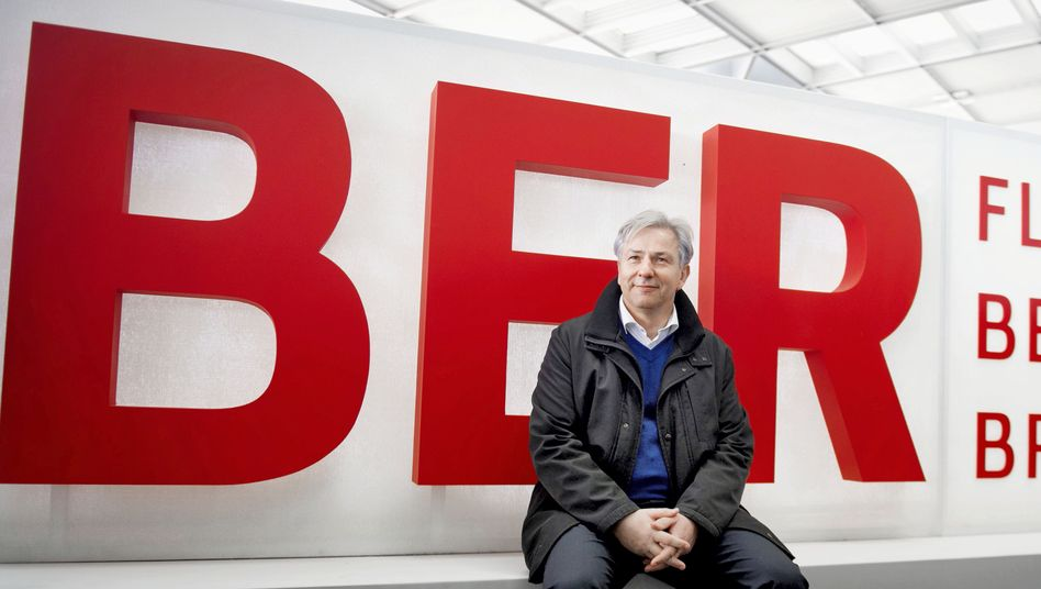 Berlin Mayor Klaus Wowereit sits on a sign at Berlin's BER Airport, whose opening has been delayed until next year.