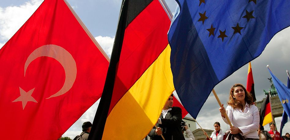 Young people of Turkish descent waving Turkish and German flags in Berlin.