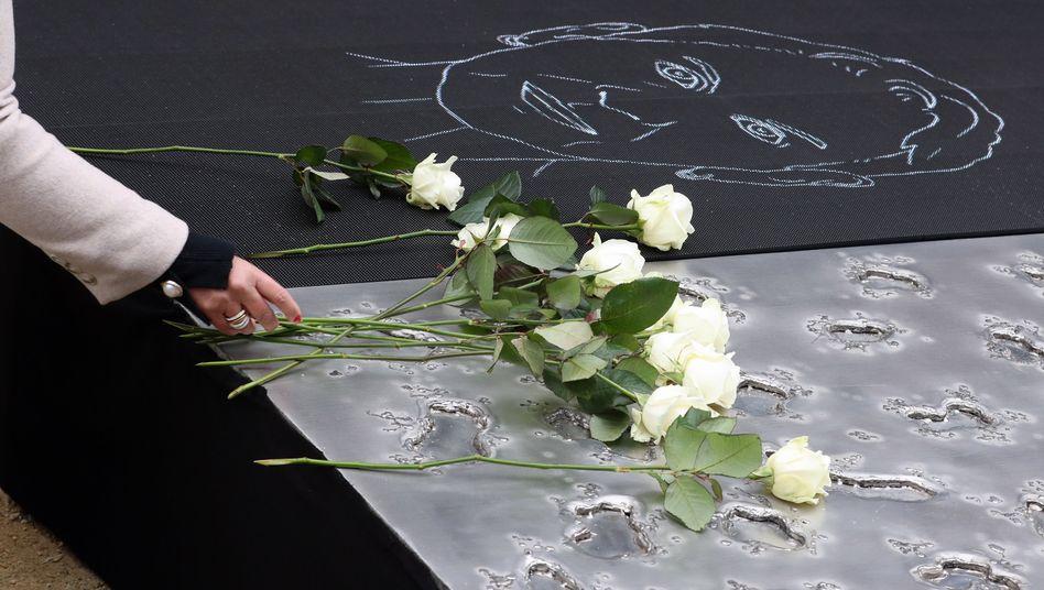 Angehörige legen weiße Rosen auf dem Denkmal für die Opfer der Terroranschläge vom 2016 nieder