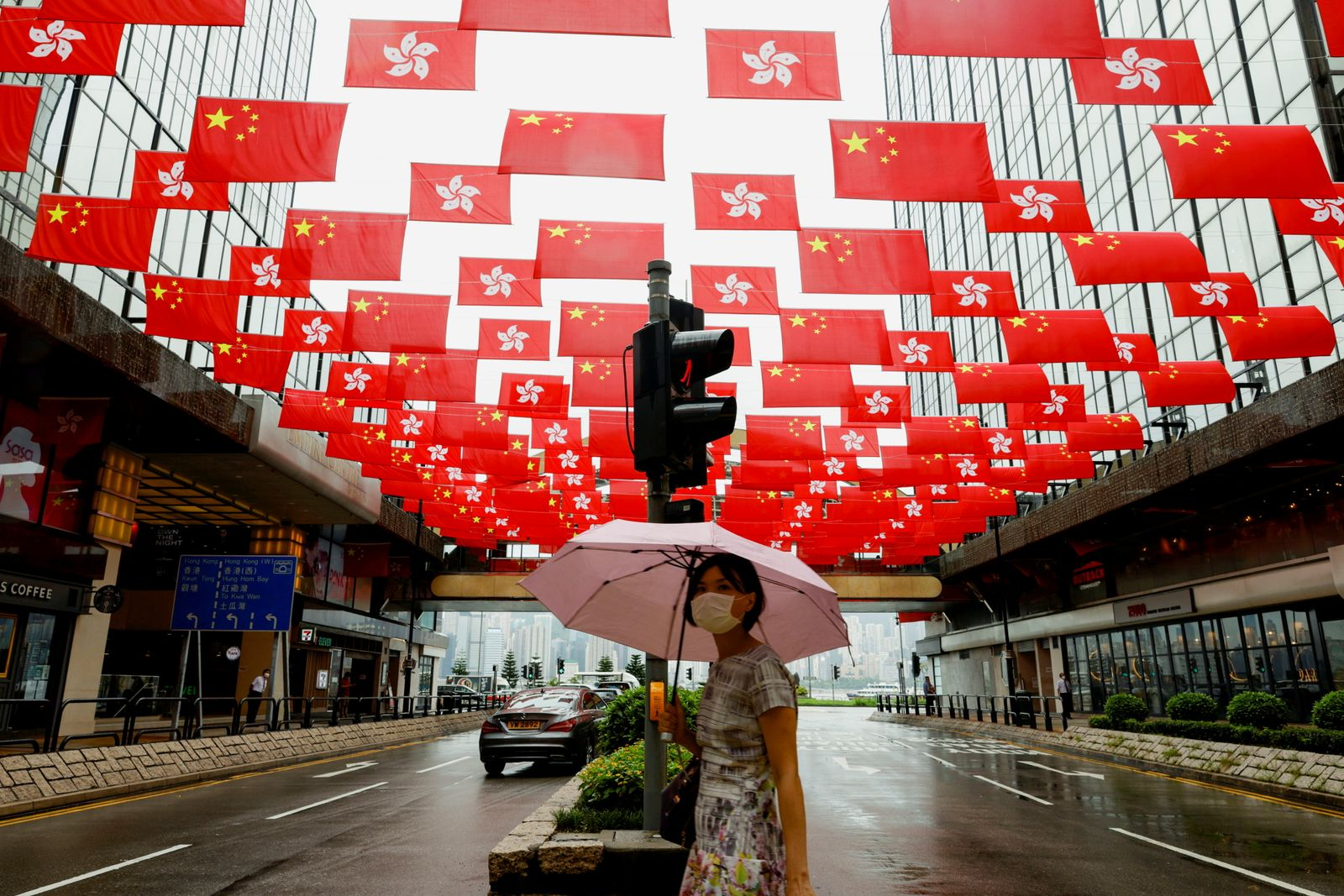 A woman walks under China and Hong Kong's flags hanging outside a shopping mall ahead of the 100th founding anniversary of the Communist Party of China, in Hong Kong