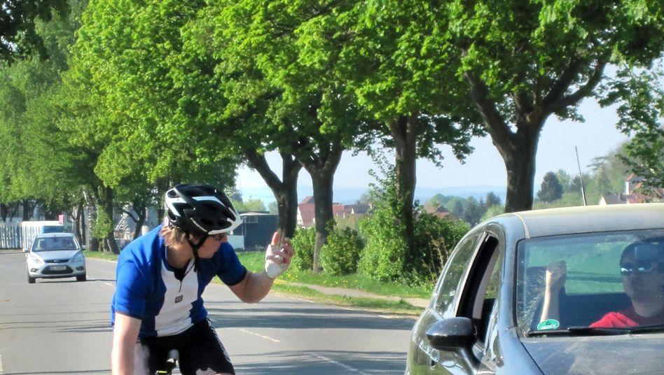 Straßenkampf: Ein Radler und ein Autofahrer beschimpfen sich