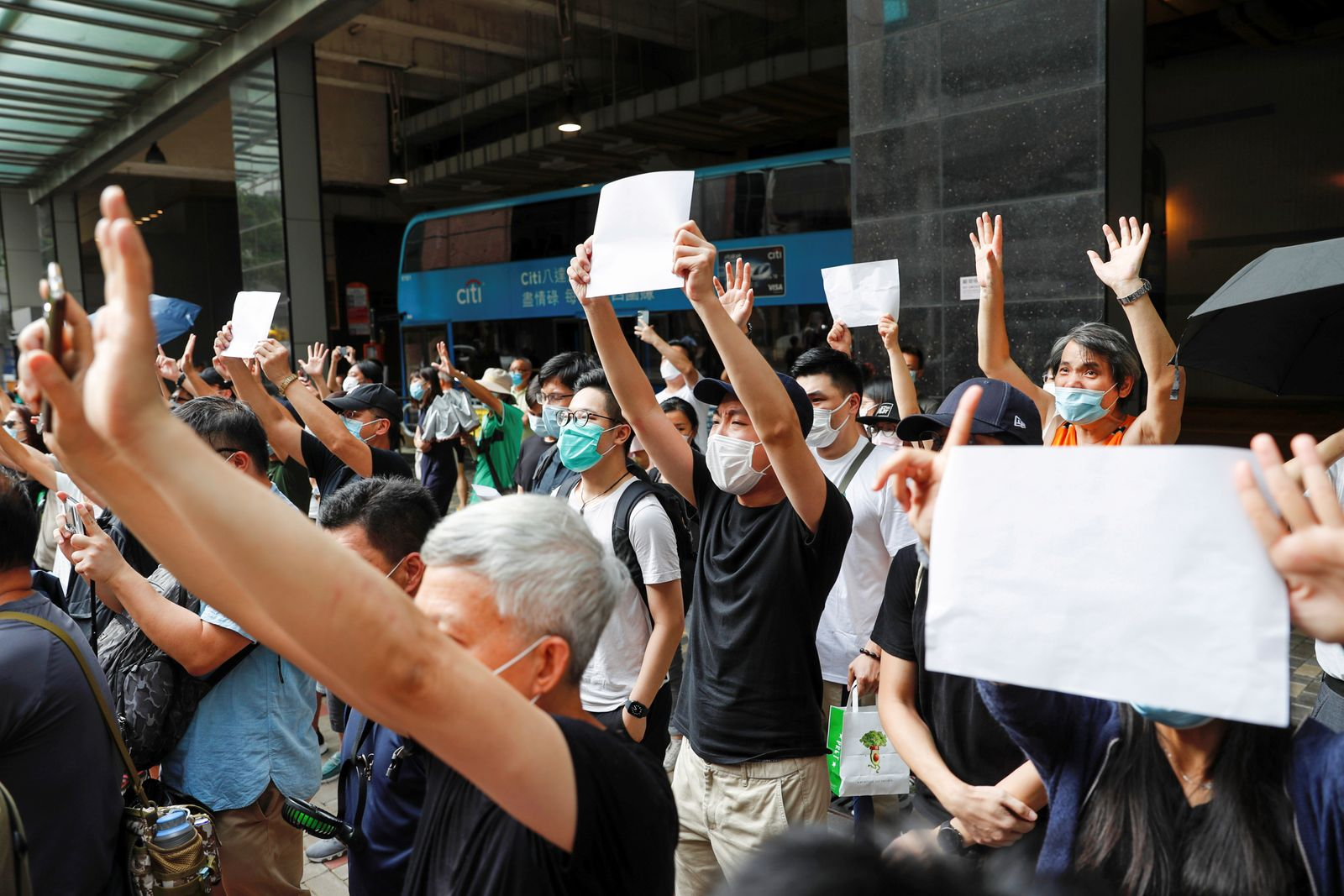 FILE PHOTO: Supporters raise blank white paper to avoid slogans banned under the national security law as they support an arrested anti-law protester outside Eastern court in Hong Kong
