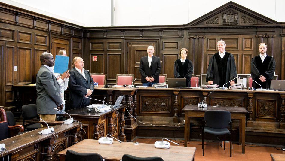 Angeklagter (2.v.l.) im Landgericht Hamburg zwischen einem Dolmetscher und seinem Anwalt (Archiv)