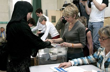 A Muslim voter (L) casts her ballot for the presidential elections 1st round in Paris, France, 22 April 2007. Although some 5 million Muslims live in France it is not considered their vote as a 'Muslim one'. According to recent pools favorites to get into 2nd round are Nicolas Sarkozy and Segolene Royal, but Francois Bayrou appears as also being a serious contender. EPA/LUCAS DOLEGA +++(c) dpa - Bildfunk+++