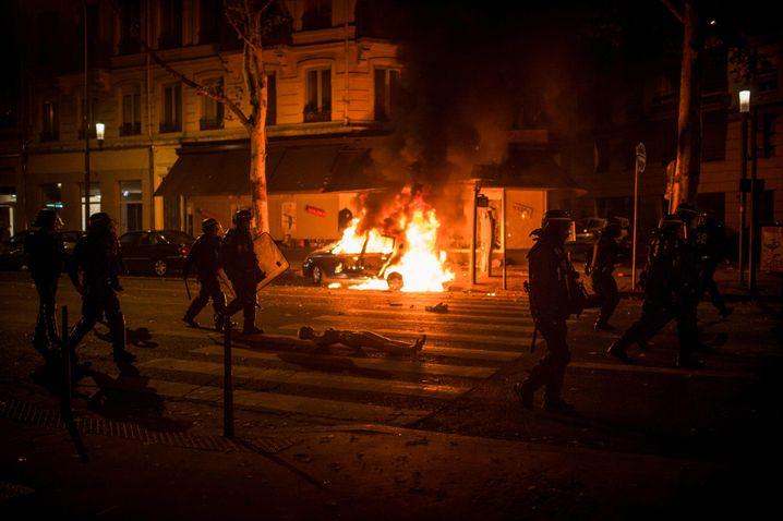 Polizisten vor einem brennenden Auto in Lyon