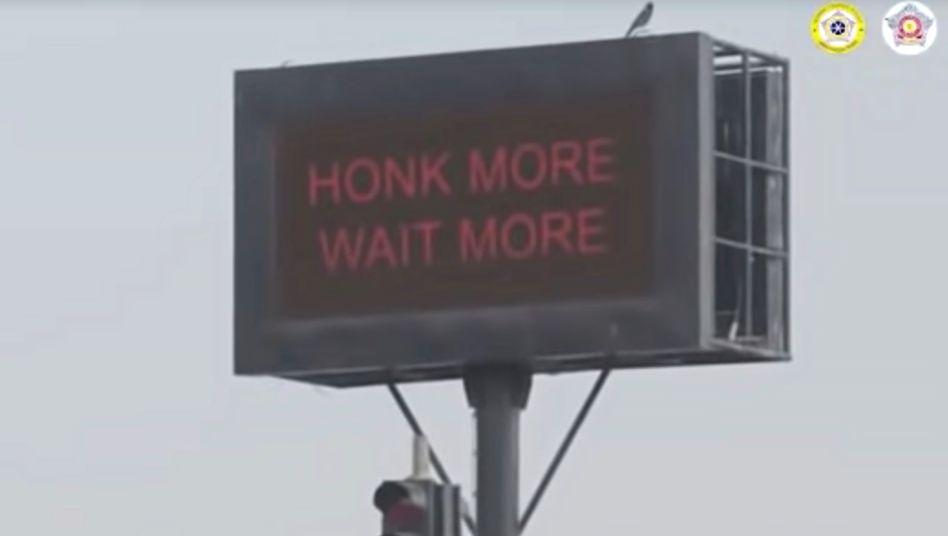 """""""Wer mehr hupt, muss länger warten"""". Eine Informationstafel weist die Autofahrer auf ein neues Ampel-System hin"""