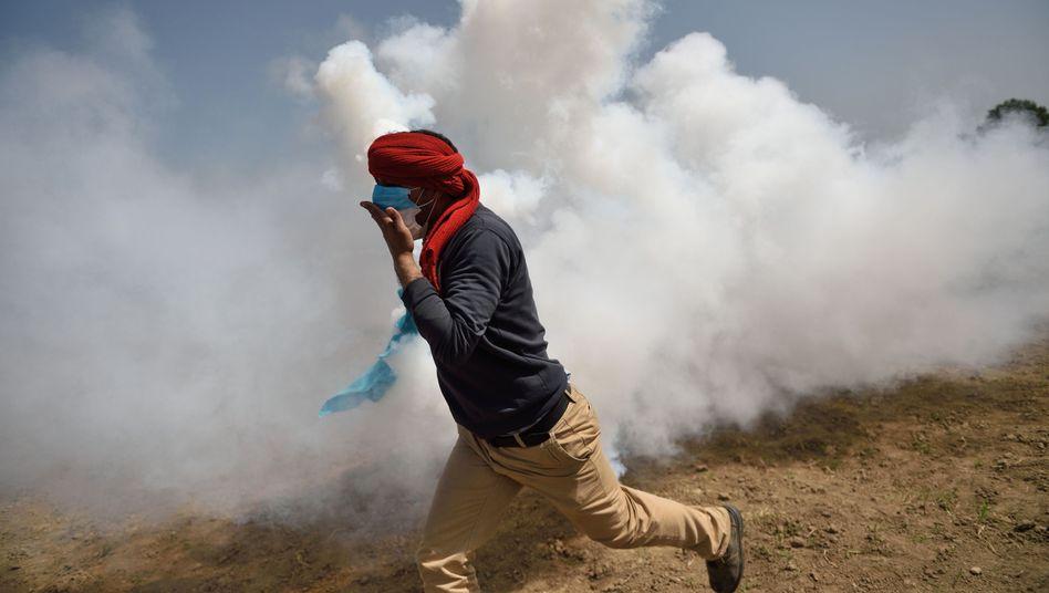 Mann flüchtet vor Tränengaswolke in Idomeni