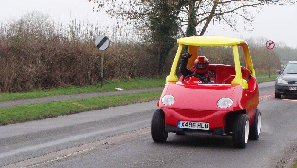 Überdimensionales Spielzeugauto: Kindskopf am Steuer