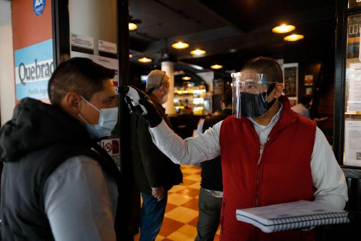 Ein Kellner mit Maske misst die Temperatur von Gästen und bittet sie, die Hände zu desinfizieren