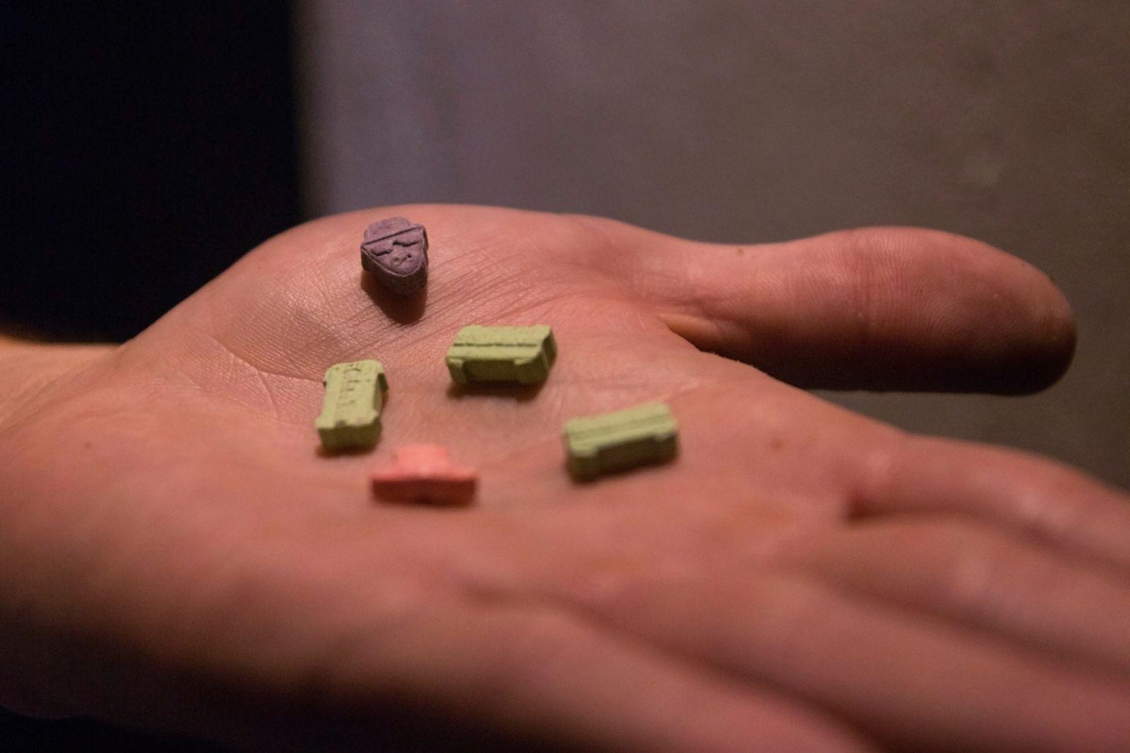 Ecstasy pills on a man's hand.