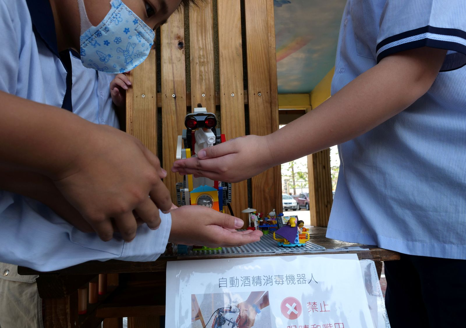 Elementary school students use a self-built motion sensor controlled disinfectant dispenser assembled with Lego parts, following a novel coronavirus outbreak, in the southern Taiwanese city of Kaohsiung, Taiwan