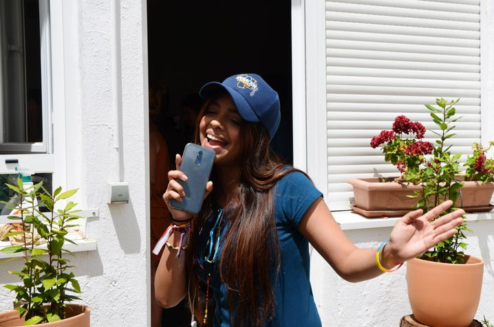 Zuleta's daughter sings into her smartphone.