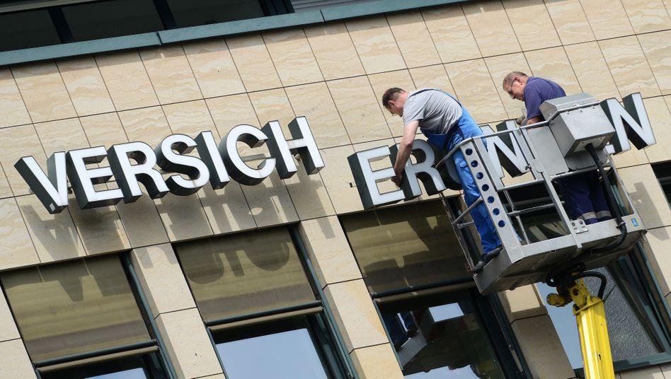 Zwei Männer wechseln Schriftzug an einer Fassade aus